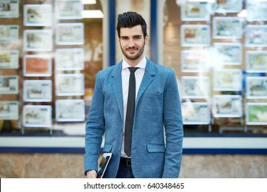 Outdoor portrait of confident, young real estate agent standing front of agency.