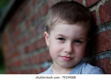 Outdoor portrait of cute boy near brick wall