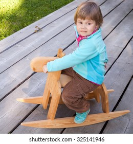 Outdoor portrait of cute Caucasian blond baby girl riding small wooden horse toy