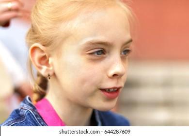 Outdoor portrait of cute Caucasian blond girl near house