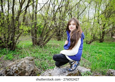 Outdoor portrait of a cute kid girl with long brunette hair on sunset, playing in the park