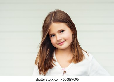 Outdoor portrait of cute little 8-9 year old girl with brown hair, wearing white jacket, standing against white background