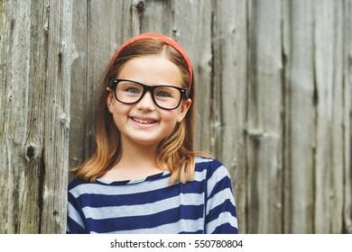 0cc1aa314315 Outdoor portrait of a cute little 9 year old girl wearing eyeglasses