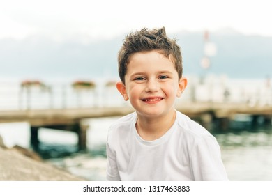 Outdoor portrait of cute little boy resting by the lake on a nice day