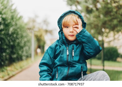 Outdoor portrait of cute little boy pretending taking photos with his hand, child wearing warm waterproof blue jacket