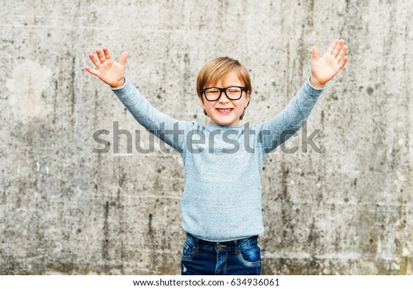 Outdoor portrait of a cute little boy wearing eyeglasses, light blue pullover and denim jeans