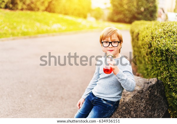Outdoor portrait of a cute little boy wearing eyeglasses, light blue pullover and denim jeans, holding bottle drink with a straw