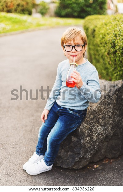 Outdoor portrait of a cute little boy wearing eyeglasses, light blue pullover, denim jeans and white baskets, holding drink with a straw