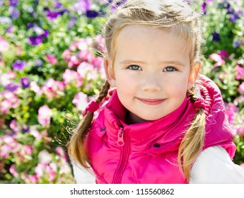 Outdoor portrait of cute little girl near the flowers in spring day