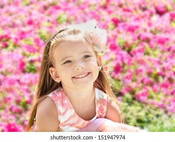 Outdoor portrait of cute little girl near the flowers in summer day