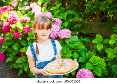 Outdoor portrait of a cute little girl with apple pie going to neighborhood party