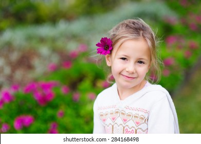 An outdoor portrait of a cute little girl smiling with a flower in her hair and purple flowers in the background
