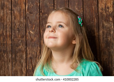 Outdoor portrait of a cute little girl standing next wooden door, wearing turquoise shirt ,and bobby pin in her hair..