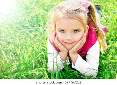 Outdoor portrait of cute little girl lying in the grass on the meadow