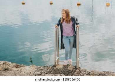 Outdoor portrait of cute preteen girl , playing next to lake, wearing purple t-shirt and blue denim jeans