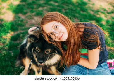 Outdoor portrait of cute red-hired kid girl hugging her dog Finnish Lapphund