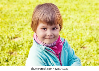 Outdoor portrait of cute smiling Caucasian blond baby girl walking in a summer park