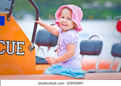 Outdoor portrait of a cute toddler girl sitting in a surf rescue boat