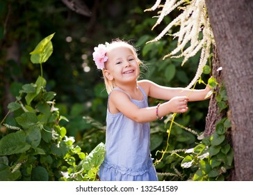 Outdoor portrait of a cute toddler girl holding to a tree and smiling into camera