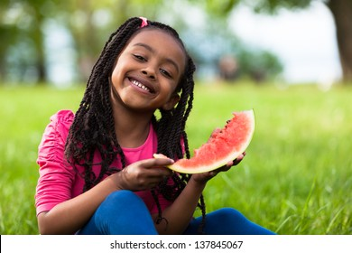 Outdoor portrait of a cute young black little  girl eating watermelon - African people