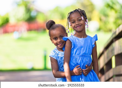 Outdoor  portrait of a cute young black sisters smiling - African people - African people