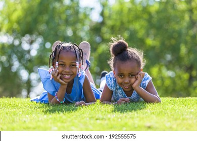 Outdoor portrait of a cute young black sisters  lying down on the grass and smiling - African people