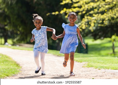 Outdoor  portrait of a cute young black sisters running - African people