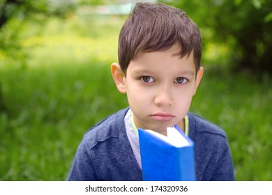 Outdoor portrait of a cute young little boy reading a book