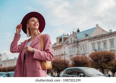 Outdoor portrait of elegant smiling woman wearing stylish pink blazer,  with yellow shoulder bag, posing in street of European city. Copy, empty space for text