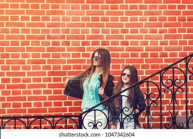 Outdoor portrait of fashion mom and daughter on brick background