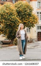 Outdoor portrait of fashion woman wearing long beige cardigan