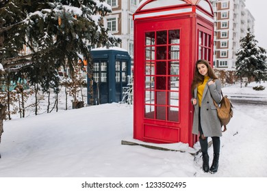 Outdoor portrait of fashionable brunette girl with backpack posing beside red call-box during weekend in England. Full-length photo of refined woman in gray coat smiling near phone booth in winter.