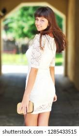 Outdoor portrait of female model in white dress