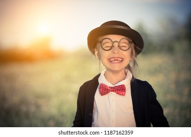 bf3686171d36 Outdoor portrait of funny happy little girl in bow tie and bowler hat.  Retro stile