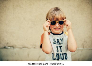 """Outdoor portrait of funny little boy wearing sunglasses and t-shirt with sign """"Say It Loud"""""""