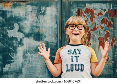 """Outdoor portrait of funny little boy wearing glasses and t-shirt with sign """"Say It Loud"""""""