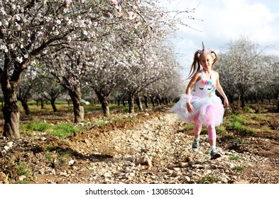 Outdoor portrait of girl in a unicorn costume. Spring is around, apple trees are blooming.
