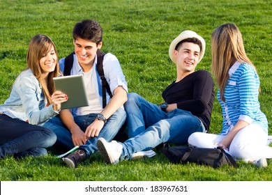 Outdoor portrait of group of friends having fun with digital tablets