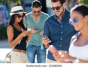 Outdoor portrait of group of friends having fun with smartphones.