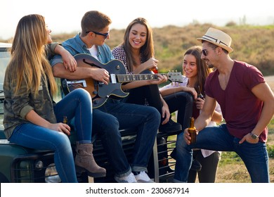 Outdoor portrait of group of friends playing guitar and drinking beer.