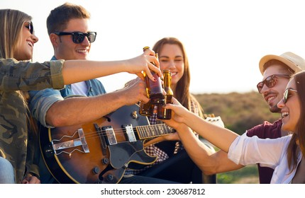 Outdoor portrait of group of friends toasting with bottles of beer.
