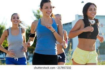 Outdoor portrait of group of women running in the park.