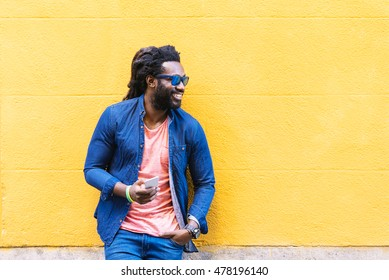Outdoor Portrait Of Handsome African Young Man Using Mobile In The Street.