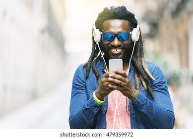 Outdoor Portrait Of Handsome African Young Man Writing Message And Listening Music.