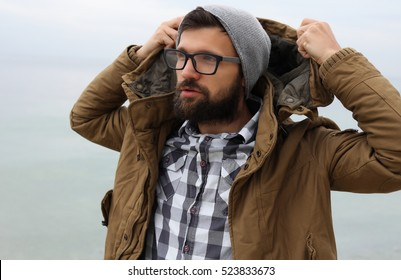 Outdoor Portrait of a handsome brutal bearded man with dark beard and mustache dressed in winter clothes,covered with frost.man in glasses,handsome man wear coat and grey hat.hipster man style
