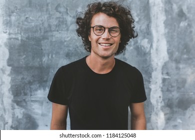 Outdoor portrait of handsome freckled smiling male with curly hair, wears sepctacles posing for social advertisement, isolated on gray concrete wall with copy space for your promotional information