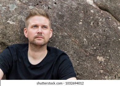 Outdoor portrait of handsome mid adult man with rugged stubble beard looking away