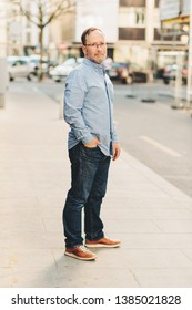 Outdoor portrait of handsome middle age man wearing long sleeve Oxford shirt, posing on city street, holding hand in jeans pocket