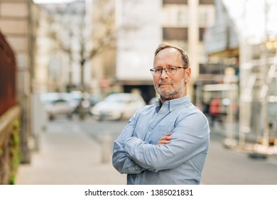 Outdoor portrait of handsome middle age man wearing long sleeve Oxford shirt, posing on city street, arms crossed