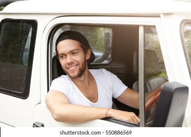 Outdoor portrait of handsome young bearded male in baseball cap sticking out his head out of open window of his white car smiling, enjoying wild life from inside during safari adventure trip